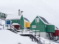 groene houten huizen op met sneeuw bedekte helling onder witte luchten