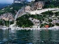 bílá loď na vodní hladině poblíž hory během dne