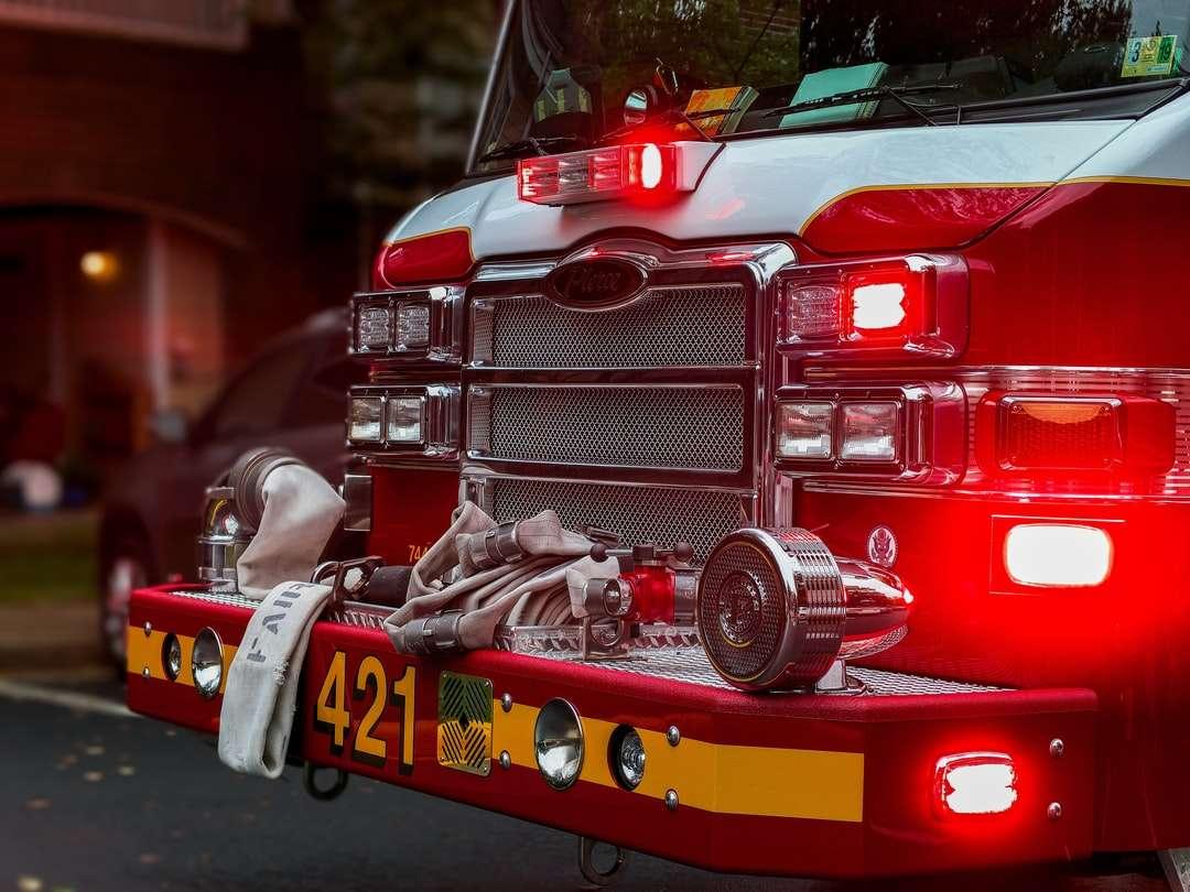 czerwono-czarny samochód z soczewką z przesunięciem pochylenia - Wóz strażacki przewożący ratowników i wyposażony w światła awaryjne - zaparkowany przed apartamentowcem w Fairfax w Wirginii (5×4)