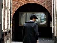 човек, който се разхожда по улицата близо до бялата сграда