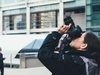 nő visel szürke és fekete kabátot DSLR fényképezőgéppel