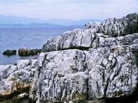 сива скална формация близо до водното тяло през деня