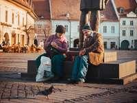nő ül a férfiak mellett szobor közelében