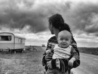 šedé fotografie ženy, která nosí dítě hledá