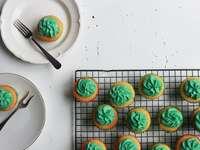 cupcakes com coberturas verdes e dois pratos com um cupcake