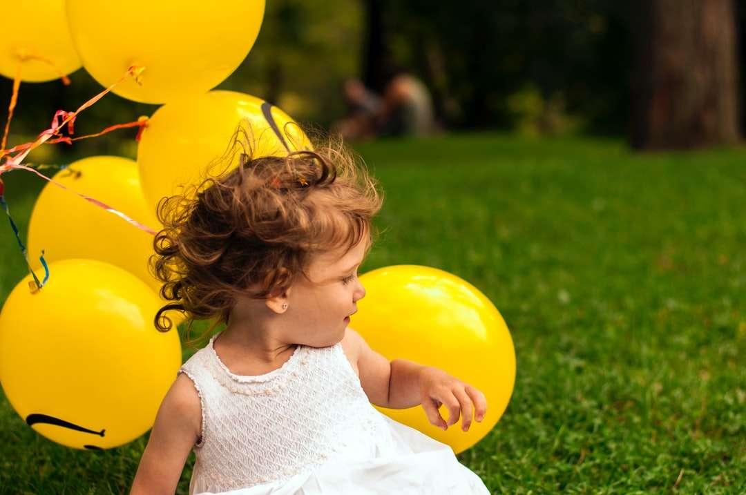 Mädchen, das auf Gras nahe Ballon sitzt