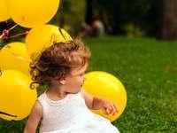 meisje zittend op het gras in de buurt van ballon