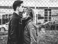 Foto en escala de grises del hombre besando la frente de la mujer cerca de la valla