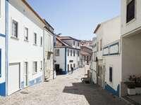 сив път, облицован с бели и сини бетонни къщи