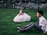 dziewczyna siedzi na zielonej trawie patrząc na chłopca