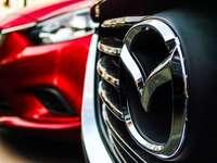 Emblema da Mazda na grade ao lado do carro vermelho estacionado