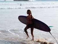 γυναίκα σε μαύρο μπικίνι κρατώντας μπλε σανίδα του σερφ στην παραλία
