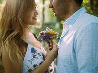 мъж и жена, обърнати един към друг, докато държат цветя