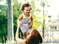 selektivní zaměření fotografie ženy zvedání dítěte během dne