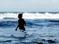 žena drží bílé surfovací prkno na vodě