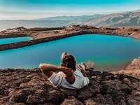 žena v bílé košili sedí na hnědé skále poblíž jezera
