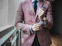 άντρας σε καφέ σακάκι κοστούμι δίπλα σε παράθυρο με κιγκλιδώματα
