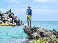 Hombre con camiseta azul de pie sobre una roca gris en el mar