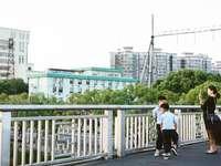 мъж в бяла тениска и черни къси панталони, бягащи по пътя
