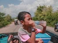 osoba pijąca wodę butelkowaną w pickupie