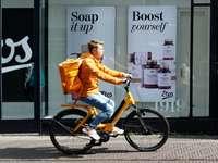 Homme en veste orange à vélo pendant la journée