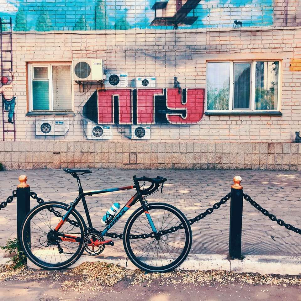 czarny rower zaparkowany obok niebiesko-białego betonowego budynku