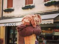 osoba trzymająca brązowy rożek lodów