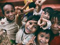 cinci copii zâmbind în timp ce fac semnul mâinii păcii
