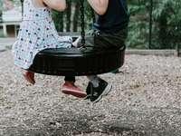 dvě děti si hrají na houpačce pneumatik