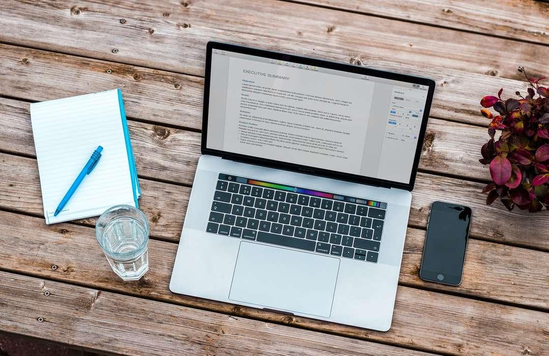 сребърен MacBook до космически сив iPhone 6 и прозрачна чаша за пиене пъзел