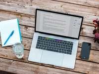 srebrny MacBook obok iPhone'a 6 w kolorze gwiezdnej szarości i przezroczystej szklanki