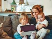 doi bebeluși și o femeie care stau pe canapea