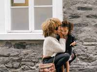 mulher com suéter branco carregando uma filha