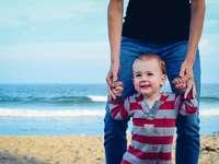 bărbat care ajută copilul să meargă pe plajă
