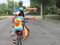 mulher de vestido azul e vermelho andando de bicicleta na estrada