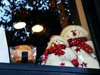 weißes Schneemannplüschtier auf Glasfenster