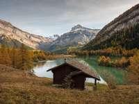 casa de madeira marrom no lago perto de montanhas verdes e marrons