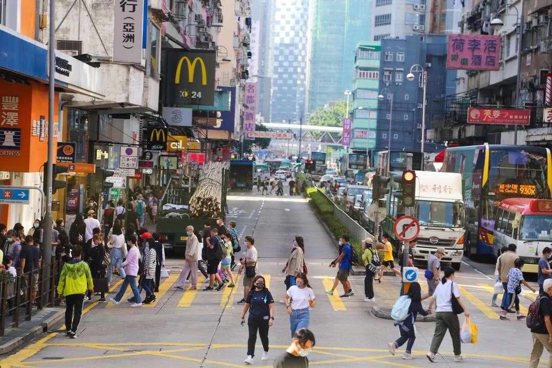 personnes marchant sur une voie piétonne pendant la journée