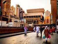 járdán barna betonépület közelében járó emberek