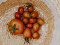 orange und rote Tomate auf braun gewebtem Korb