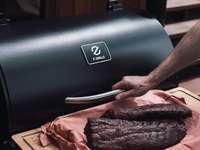 Persona sosteniendo carne cruda sobre una tabla de cortar de madera marrón
