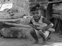 grayscale photo of boy in tank top sitting on concrete wall