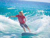 момиче в червен потник и сини шорти, сърфиращи по вода