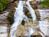 water falls on brown rocky mountain