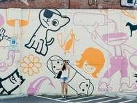 upřímná fotografie ženy stojící proti graffiti zdi