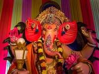 socha hinduistického božstva před fialovou oponou