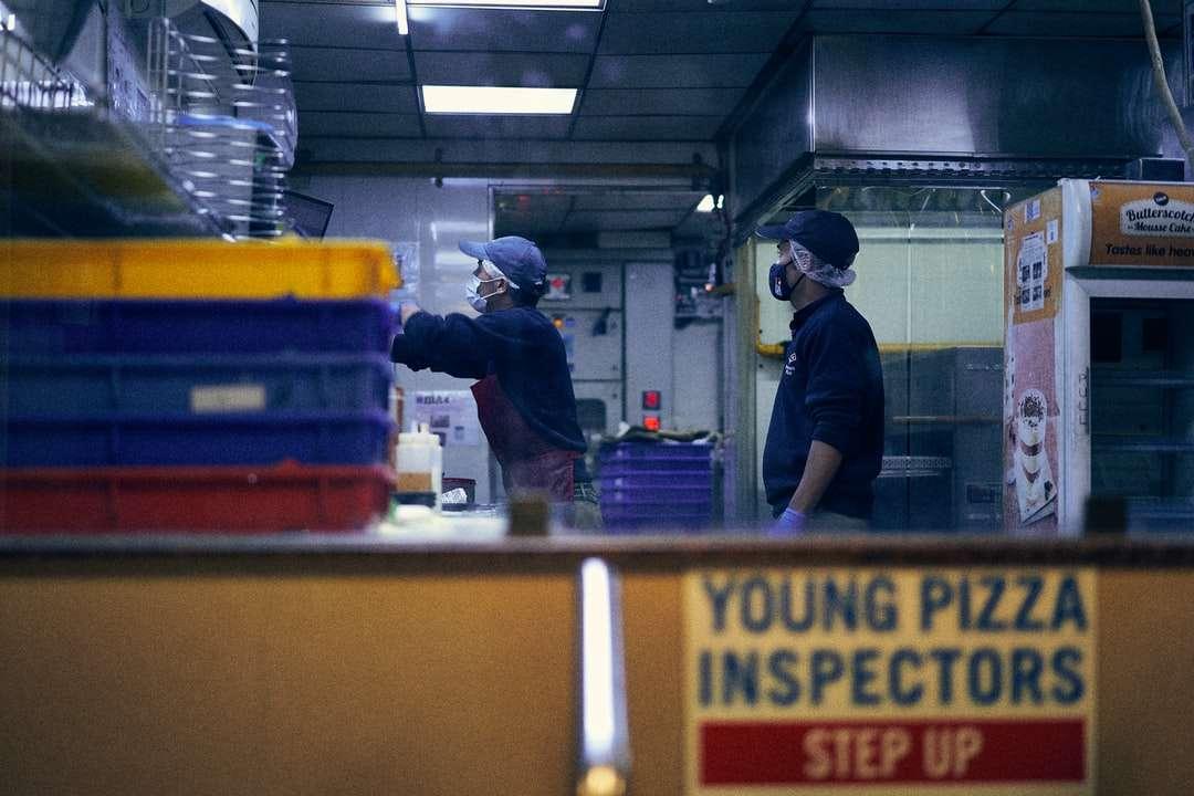 homme en t-shirt bleu - homme en t-shirt bleu debout près de bouteille en plastique étiquetée jaune et blanche. Deux hommes portant des masques travaillant chez Domino. Domino's Pizza Nainital 263001, Mall Road, Mallital, (4×3)