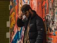 muž v černé bundě stojící vedle zdi graffiti