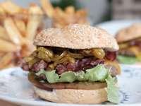 burger z sałatą i pomidorem na białym talerzu ceramicznym