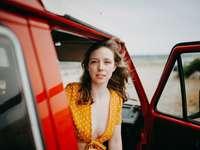 Mujer en vestido amarillo sin mangas de pie junto al coche rojo